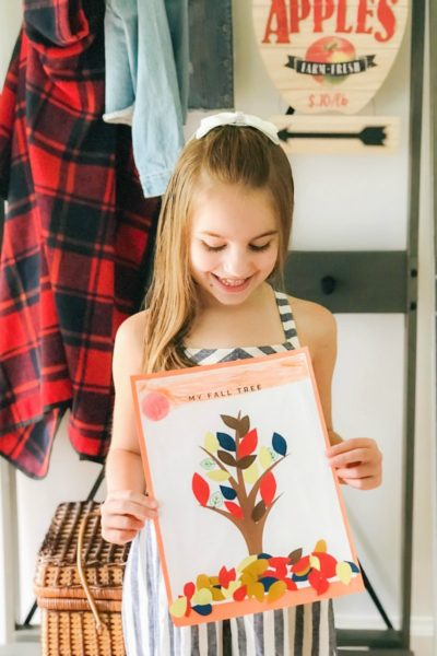 girl holding fall tree craft